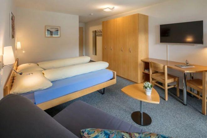 Hotel-Seebuel-Superiorzimmer-Schlafzimmer-Fernseher-Couch